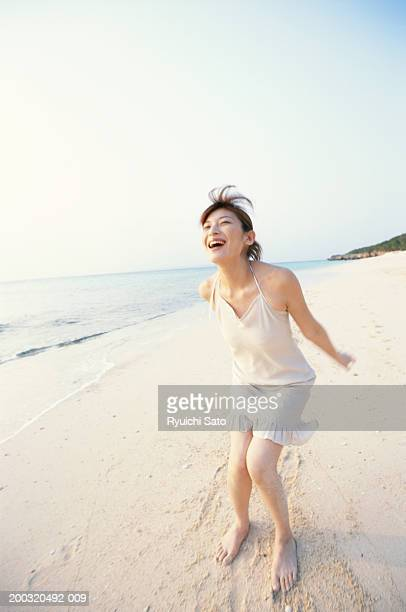 Woman standing on beach, laughing