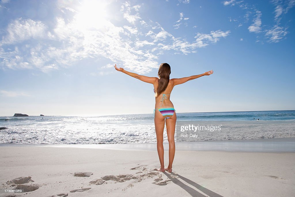 Woman standing on beach with arms outstretched : Stock Photo