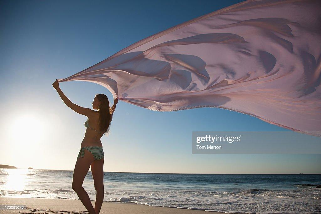 Donna in piedi sulla spiaggia con un tessuto : Foto stock