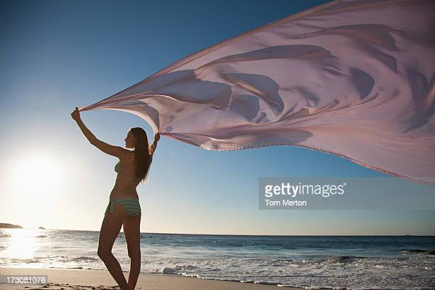 Woman standing on beach with fabric