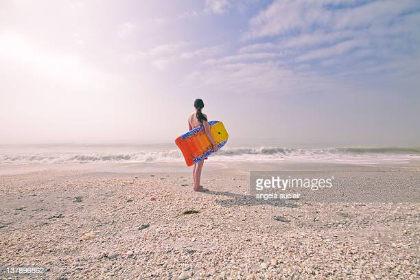 Woman standing on beach with surfboard