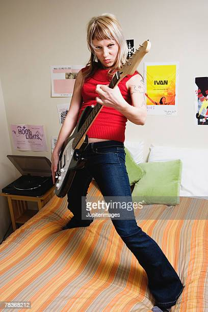Woman standing on bed playing electric guitar