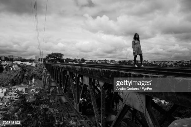 Woman Standing On Bridge Against Cloudy Sky
