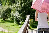 Woman standing on bridge with parasol