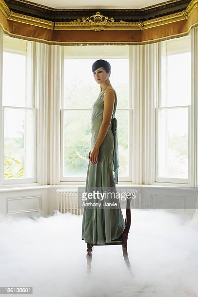 Woman standing on chair indoors with misty floor