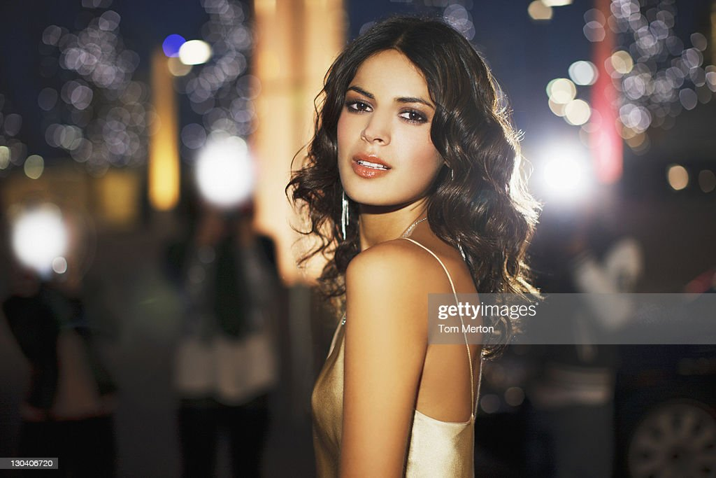 Woman standing on city street at night : Stock Photo