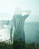 Woman standing on cliff edge, rear view (double exposure)