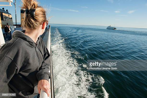 Woman standing on deck of ferry boat, looking over shoulder at view
