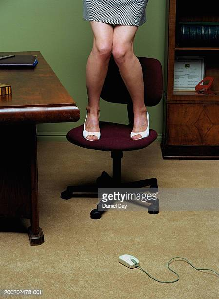 Woman standing on desk chair escaping from computer mouse on floor