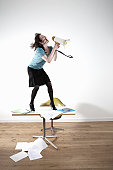 Woman standing on desk, shouting through megaphone