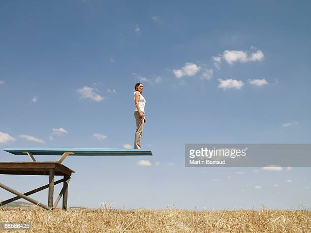 Woman standing on diving board in field