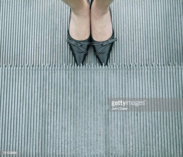 Woman standing on escalator, overhead view