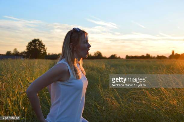 Woman Standing On Field Against Sky At Sunset