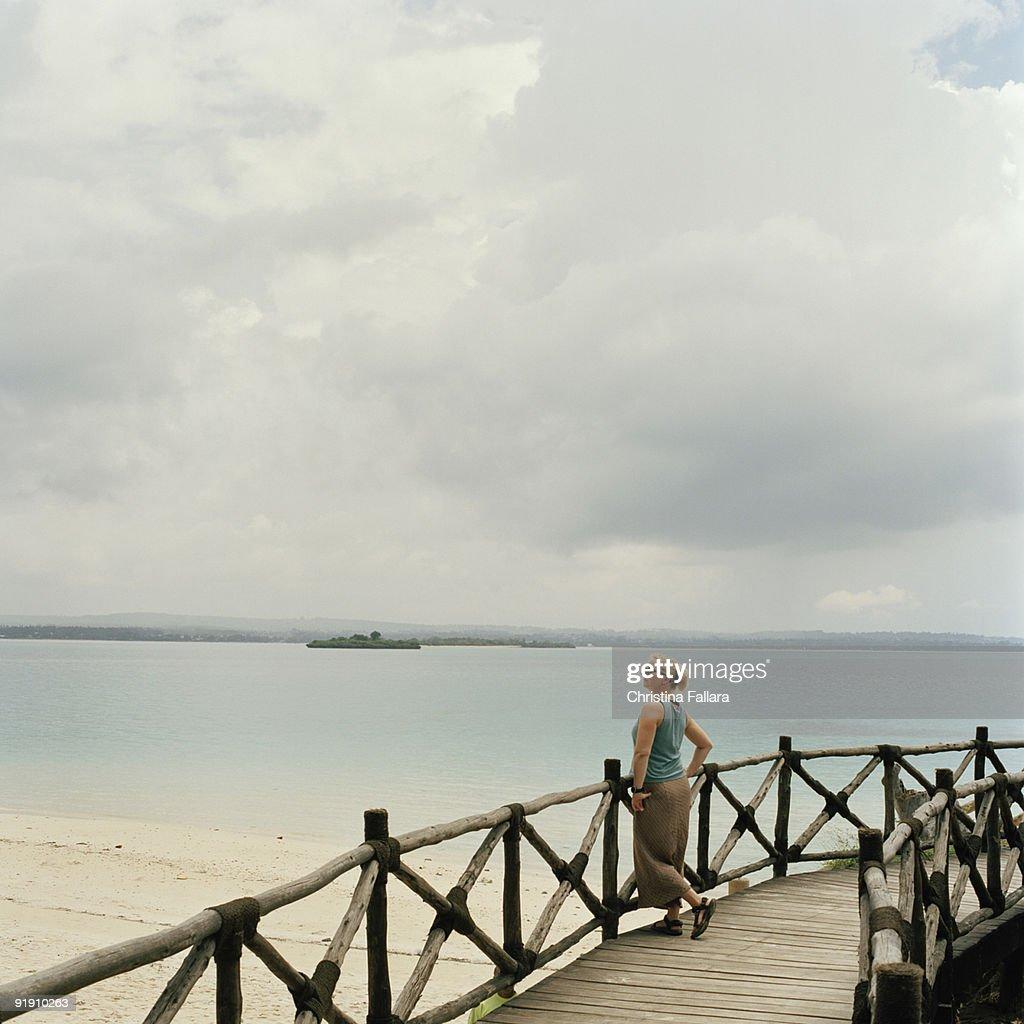 Woman standing on footbridge on Changuu Island , Zanzibar , Tanzania , Africa