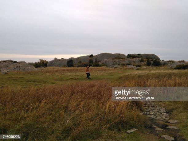 Woman Standing On Grassy Field Against Cloudy Sky