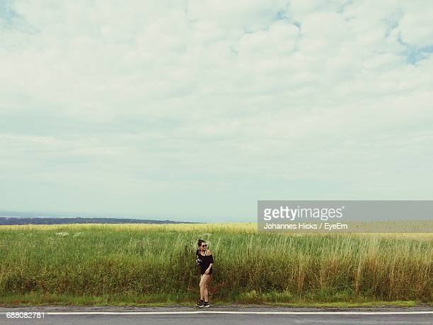 Woman Standing On Grassy Field By Road Against Cloudy Sky