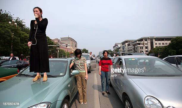A woman standing on her car cries as people stop their cars along a downtown Beijing avenue on May 19 2008 as the country observes three minutes of...