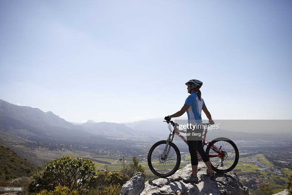 Woman standing on hill top with mountain bike : Stock Photo