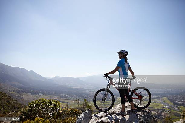 Woman standing on hill top with mountain bike