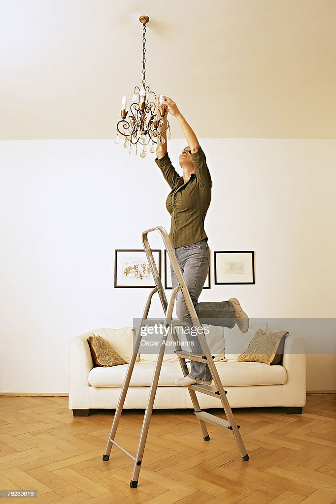 Woman Standing On Ladder Trying To Change Light Bulb In Chandelier ...