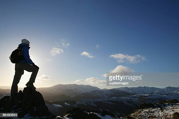 Woman standing on mountain peak
