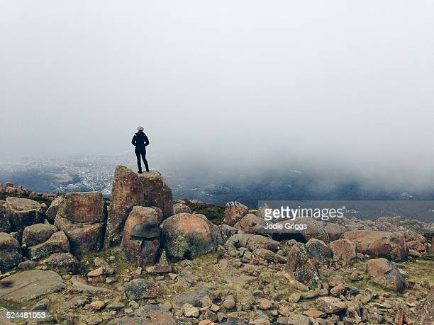 Woman standing on mountain top looking out at city