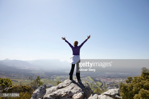 Woman standing on mountain with arms stretched out : Stock Photo
