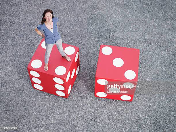 Woman standing on pair of giant dice