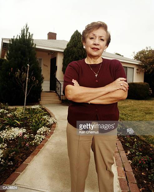 Woman standing on path in front of house, arms folded, portrait