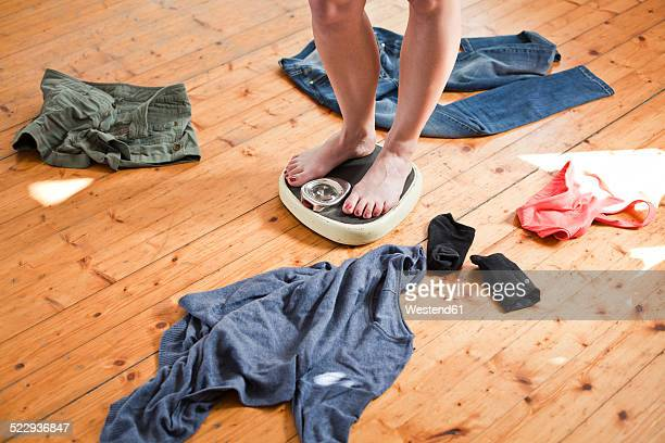 Woman standing on personal scales her clothing lying around on the floor, partial view