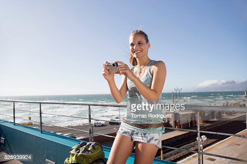 Woman standing on pier and taking picture : ストックフォト