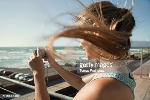 Woman standing on pier and taking picture : Foto de stock