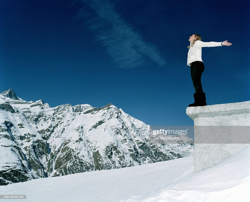 Woman standing on platform by mountain, arms outstretched, side view : Stock Photo