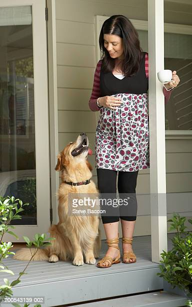 Woman standing on porch with pet dog, smiling