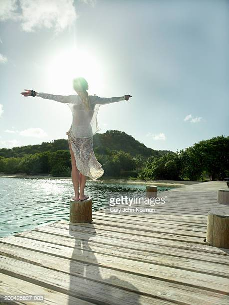 Woman standing on post with arms outstretched, rear view