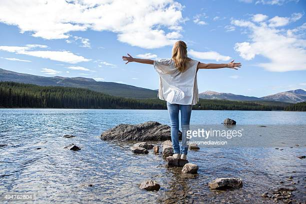 Woman standing on rock above lake arms outstretched