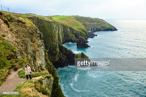 Woman standing on rock cliff by ocean Co. Cork Ireland : Bildbanksbilder