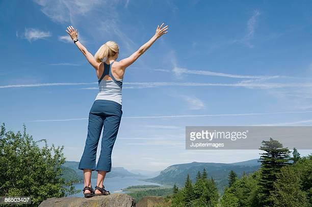 Woman standing on rock overlooking mountains