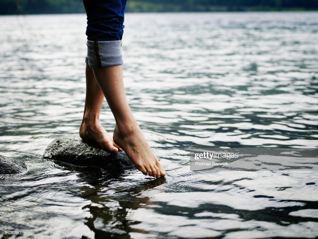 Woman standing on rock touching toes to water : Stock Photo