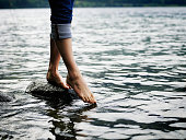 Woman standing on rock touching toes to water