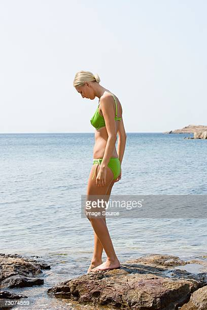 Woman standing on rocks by the sea