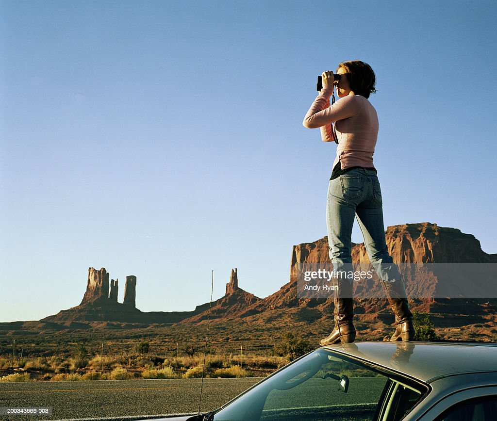 Woman standing on roof of car, using binoculars, side view : Stock Photo