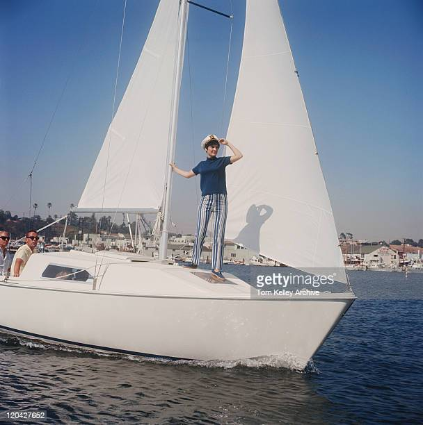 Woman standing on sailing boat, two men in background