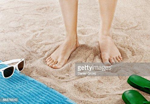 Woman standing on sandy beach, close-up of feet : Stock Photo