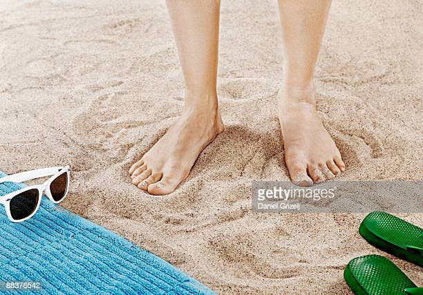 Woman standing on sandy beach, close-up of feet