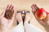 Woman standing on scales and holding apple and chocolate hearts. New start for healthy nutrition, body slimming, weight loss. Cares about body. Dilemma between fruits or sweets. Decision concept.