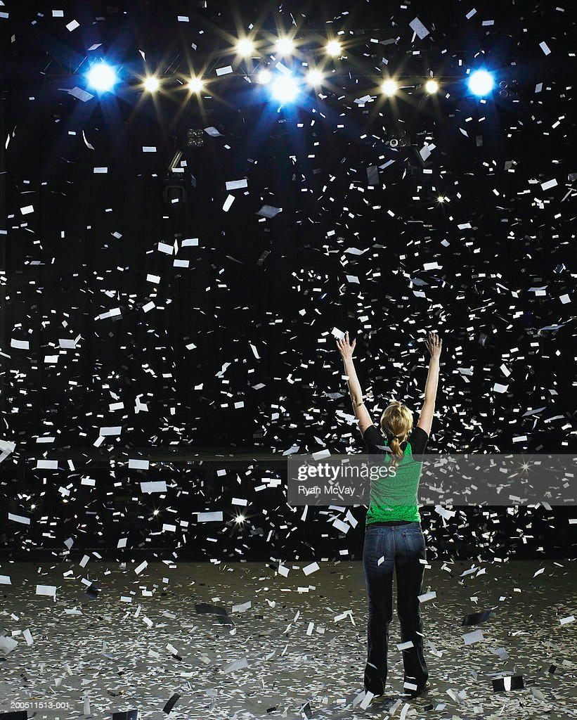 Woman standing on stage raising hands being showered with confetti : Stock Photo