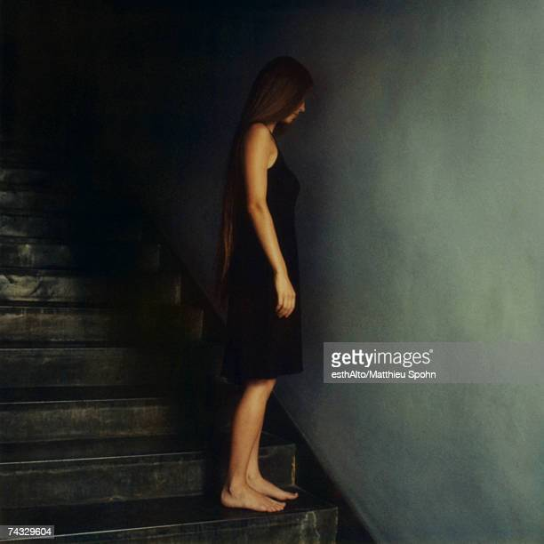 Woman standing on stairs, facing wall