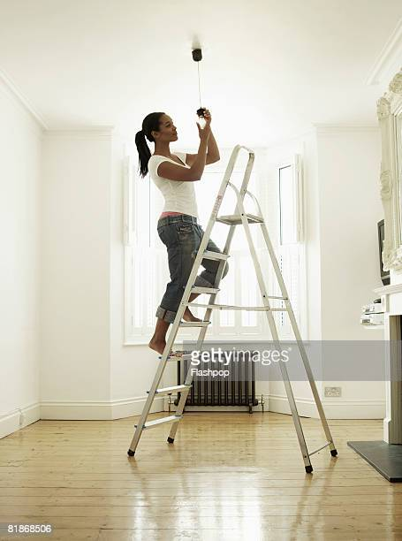 Woman standing on step ladder changing light bulb