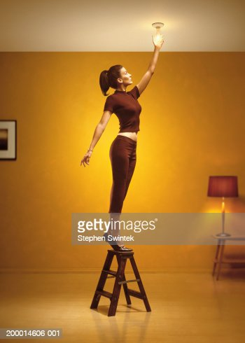 Woman standing on stepladder changing light bulb in living room